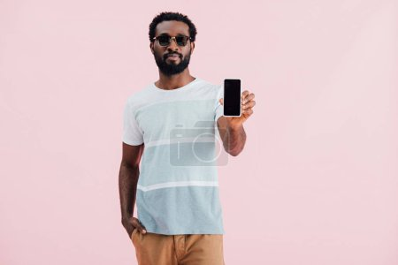 african american man in sunglasses holding smartphone with blank screen, isolated on pink