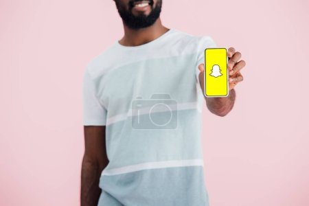 KYIV, UKRAINE - MAY 17, 2019: cropped view of african american man showing smartphone with Snapchat app, isolated on pink