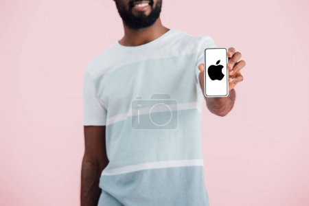 KYIV, UKRAINE - MAY 17, 2019: cropped view of african american man showing smartphone with apple app, isolated on pink