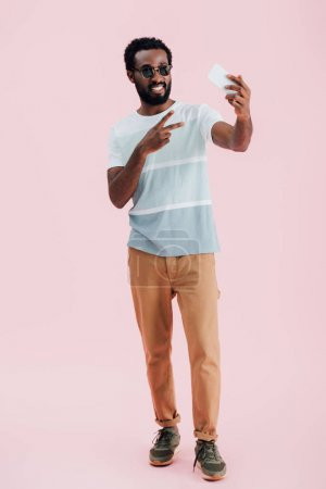 Photo pour Homme américain africain dans des lunettes de soleil avec le signe de victoire prenant le selfie sur le smartphone, d'isolement sur le rose - image libre de droit