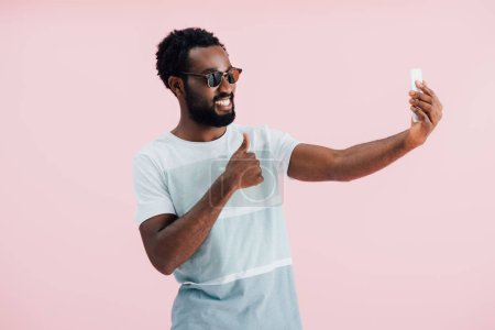 Photo for African american man in sunglasses with thumb up taking selfie on smartphone, isolated on pink - Royalty Free Image