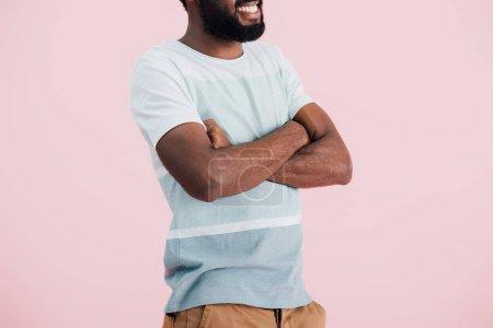 Photo pour Vue recadrée de l'américain africain de l'homme dans le t-shirt avec les bras croisés, dissous sur le rose - image libre de droit
