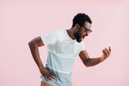 Photo for Aggressive african american of man in sunglasses shouting at smartphone, isolated on pink - Royalty Free Image
