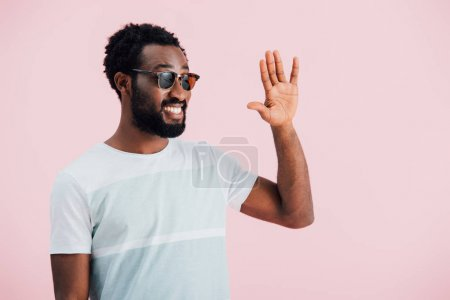 happy young african american of man in sunglasses waving isolated on pink