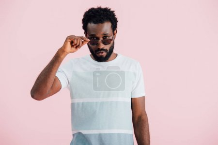 Photo pour Handsome young african american of man in sunglasses isolated on pink - image libre de droit