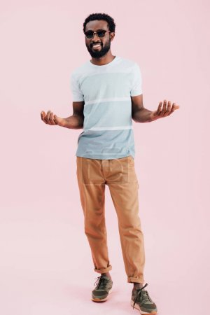 Photo for Smiling african american of man in sunglasses gesturing, isolated on pink - Royalty Free Image