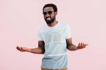 Photo pour Heureux afro-américain de l'homme en lunettes de soleil geste isolé sur rose - image libre de droit