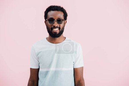 happy african american of man in t-shirt and sunglasses, isolated on pink