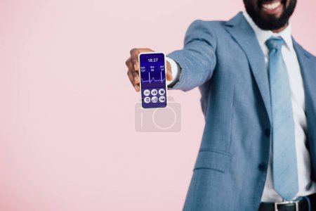 cropped view of african american businessman in suit showing smartphone with health app, isolated on pink