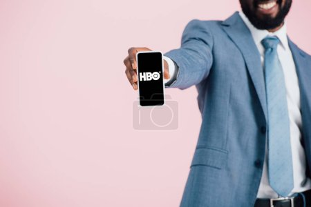 Photo for KYIV, UKRAINE - MAY 17, 2019: cropped view of african american businessman in suit showing smartphone with HBO app, isolated on pink - Royalty Free Image