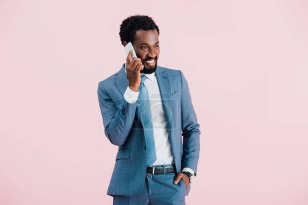 Photo pour Handsome african american businessman talking on smartphone, isolated on pink - image libre de droit