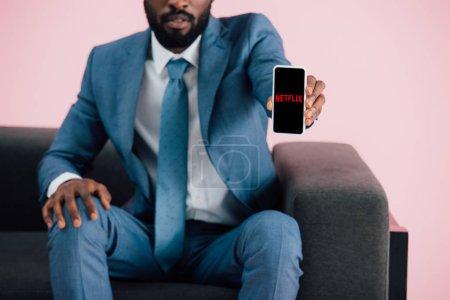 Photo pour KYIV, UKRAINE - 17 MAI 2019 : vue recadrée d'un homme d'affaires afro-américain assis sur un fauteuil et montrant un smartphone avec l'application netflix, isolé sur rose - image libre de droit