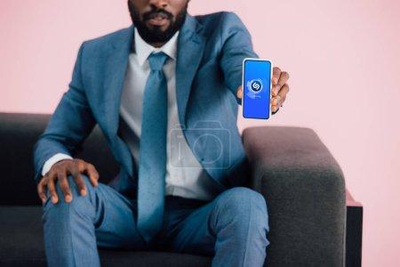 Photo pour KYIV, UKRAINE - 17 MAI 2019 : vue recadrée d'un homme d'affaires afro-américain assis sur un fauteuil et montrant un smartphone avec une application shazam, isolé sur du rose - image libre de droit