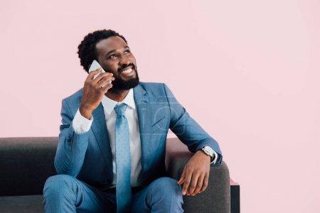 bel homme d'affaires afro-américain assis dans un fauteuil et parlant sur smartphone, isolé sur rose