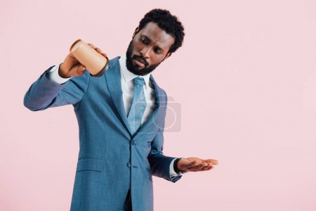Photo for Confused african american businessman looking at empty cup with coffee to go, isolated on pink - Royalty Free Image