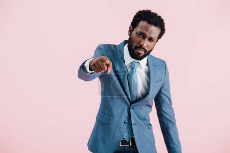 angry african american businessman in suit pointing isolated on pink
