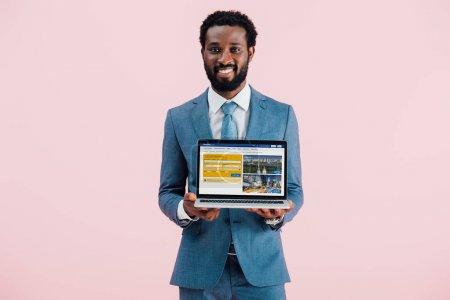 Photo pour KYIV, UKRAINE - 17 MAI 2019 : homme d'affaires afro-américain souriant montrant ordinateur portable avec site de réservation, isolé sur rose - image libre de droit