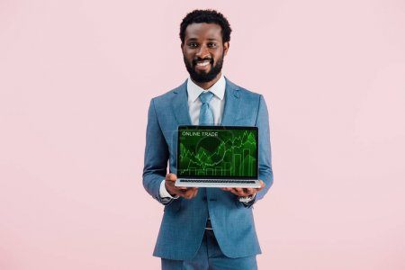 smiling african american businessman showing laptop with online trade isolated on blue
