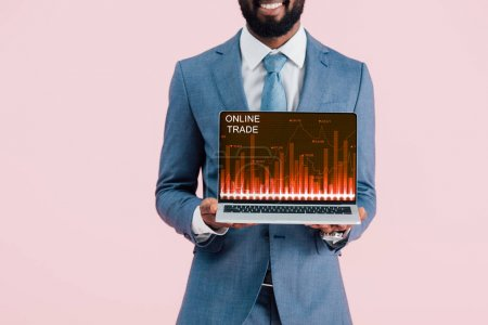 cropped view of smiling african american businessman showing laptop with online trade isolated on blue
