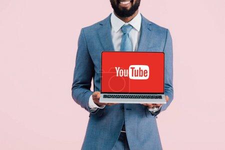 Photo pour KYIV, UKRAINE - 17 MAI 2019 : vue recadrée d'un homme d'affaires afro-américain souriant montrant un ordinateur portable avec un site Web youtube, isolé sur rose - image libre de droit