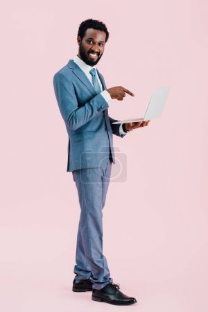 smiling african american businessman pointing at laptop isolated on pink