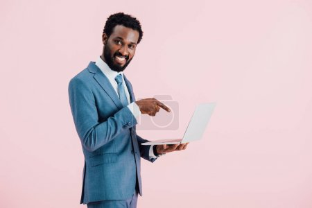 fröhlich afrikanisch-amerikanischer Geschäftsmann zeigt auf Laptop isoliert auf rosa