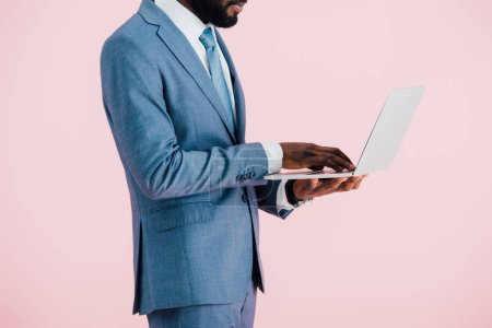 Photo for Cropped view of african american businessman in suit using laptop isolated on pink - Royalty Free Image