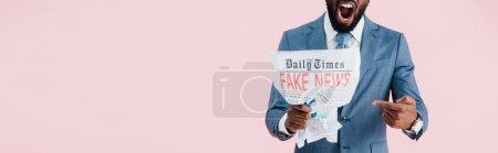 Photo pour Vue recadrée d'un homme d'affaires afro-américain en colère criant et lisant un journal avec de fausses nouvelles isolées sur rose - image libre de droit