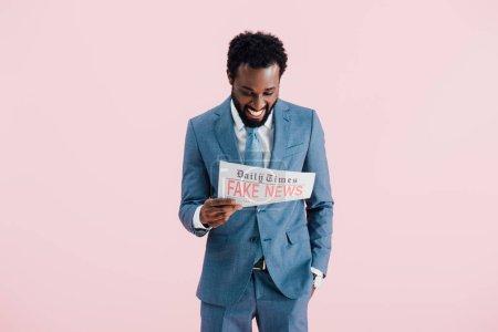 Photo pour Homme d'affaires afro-américain souriant lisant un journal avec de fausses nouvelles isolées sur rose - image libre de droit