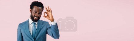 cheerful african american businessman in suit showing ok sign, isolated on pink