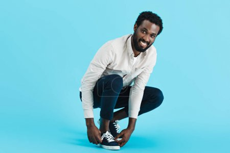 Photo for Cheerful african american man tying up laces on sneakers isolated on blue - Royalty Free Image
