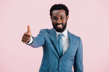 Photo for Smiling african american businessman in suit showing thumb up, isolated on pink - Royalty Free Image