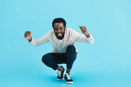 excited bearded african american man sitting isolated on blue