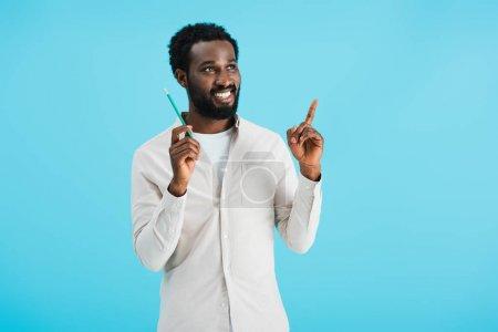 Photo pour Souriant homme afro-américain avec crayon ayant idée isolé sur bleu - image libre de droit