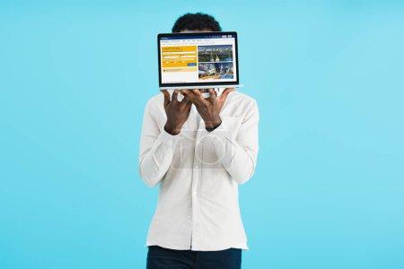 Photo pour KYIV, UKRAINE - 17 MAI 2019 : homme afro-américain montrant ordinateur portable avec site de réservation, isolé sur bleu - image libre de droit