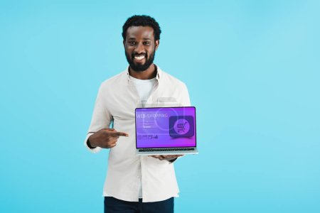 Photo for Smiling african american man pointing at laptop with web shopping website isolated on blue - Royalty Free Image