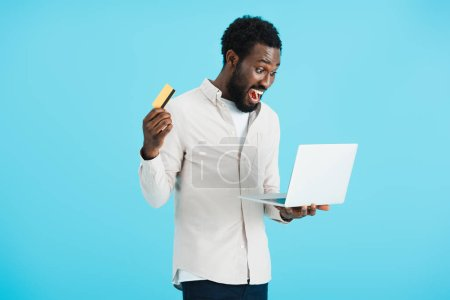 Photo for Excited african american man shopping online with credit card and laptop isolated on blue - Royalty Free Image