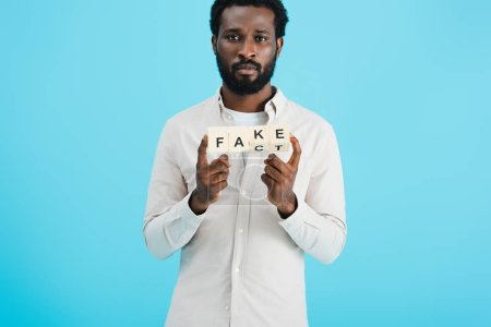 Photo for Serious african american man holding alphabet cubes with fact word, isolated on blue - Royalty Free Image