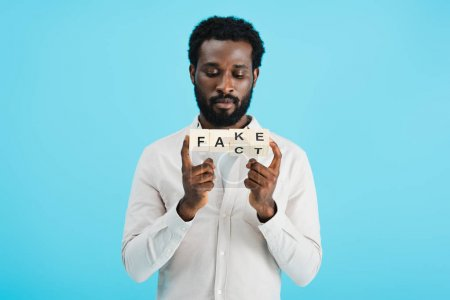 Photo pour Jeune homme afro-américain tenant des cubes d'alphabet avec mot de fait, isolé sur bleu - image libre de droit