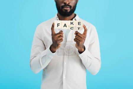 Photo pour Vue recadrée de l'homme afro-américain tenant des blocs d'alphabet avec mot de fait, isolé sur bleu - image libre de droit