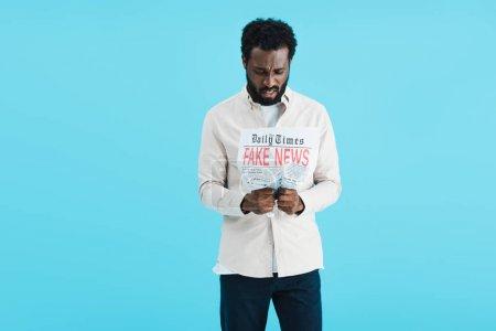 Photo pour Souligné homme afro-américain lecture journal avec de fausses nouvelles isolé sur bleu - image libre de droit