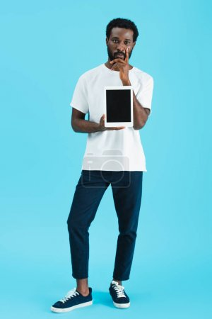 Photo for Pensive african american man showing digital tablet with blank screen isolated on blue - Royalty Free Image