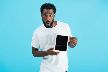 Photo pour Homme afro-américain choqué montrant tablette numérique avec écran blanc isolé sur bleu - image libre de droit