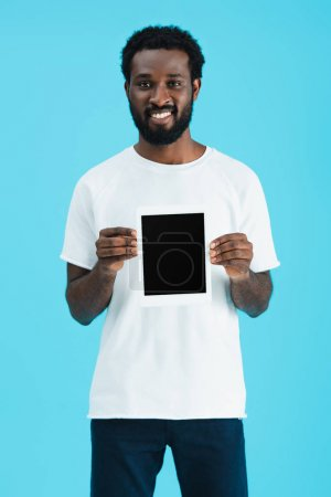 smiling african american man showing digital tablet with blank screen isolated on blue