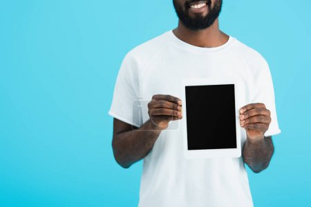 cropped view of african american man in white t-shirt showing digital tablet with blank screen isolated on blue