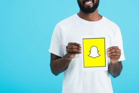 Photo pour KYIV, UKRAINE - 17 MAI 2019 : vue recadrée d'un homme afro-américain montrant une tablette numérique avec l'application Snapchat, isolé sur bleu - image libre de droit