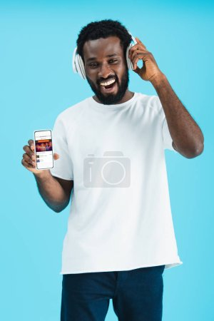 KYIV, UKRAINE - MAY 17, 2019: smiling african american man listening music with headphones and showing smartphone with soundcloud app, isolated on blue