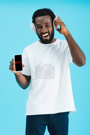 KYIV, UKRAINE - MAY 17, 2019: smiling african american man listening music with headphones and showing smartphone with netflix app, isolated on blue