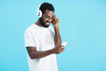 Foto de Cheerful african american man listening music with headphones and using smartphone, isolated on blue - Imagen libre de derechos