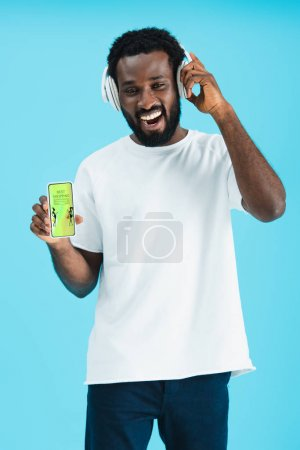 Photo pour Homme américain africain souriant écoutant la musique avec le casque et montrant le smartphone avec la meilleure application d'achat, d'isolement sur le bleu - image libre de droit